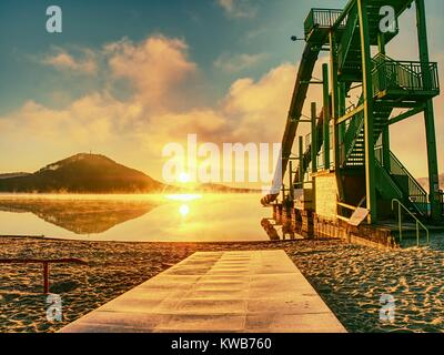 Sunset shore and toboggan slides at lake,. High ladder tower with  sliding track. Cold autumn morning with vapory - Stock Photo
