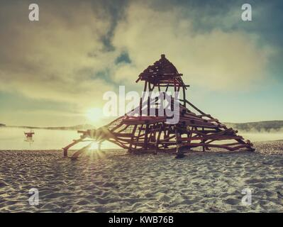 Wooden playground attraction for children in swimming bay.  Pirate ship with tower built in sand of holiday resort. - Stock Photo