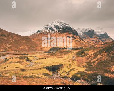 The rough mountain stream in the mountains. Snowy cone of mountain in clouds. Dry grass and heather bushes on banks - Stock Photo