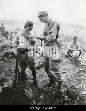 U.S. soldier of lights a cigarette for a former enemy guard. They are at a surrender conference between American - Stock Photo
