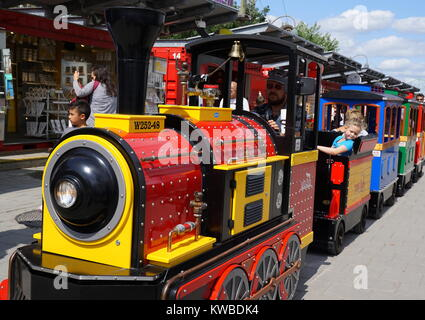 Children riding on the mini train at the Old Port of Montreal, a historic port in Old Montreal Quebec, Canada - Stock Photo