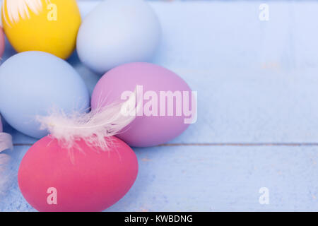 Colorful Easter eggs on a white wooden board with feathers - Stock Photo