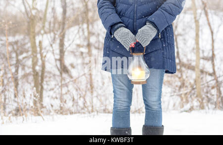 woman in fingerless gloves standing outside holding lantern while snow is falling - Stock Photo