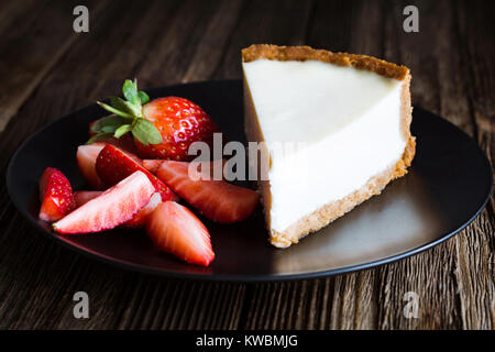 Plain New York Cheesecake with Fresh Strawberries on black plate. Closeup view, selective focus. Horizontal composition - Stock Photo