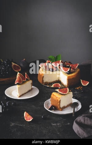 Cheesecake with figs. Sliced New York Cheesecake on dark stone background. Selective focus, toned image - Stock Photo