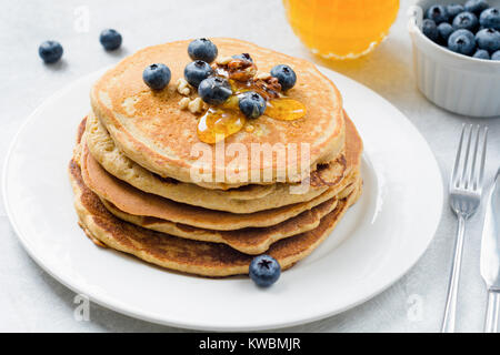Closeup view of pancakes stack with blueberries, walnuts and honey on white plate. Tasty healthy breakfast food. - Stock Photo