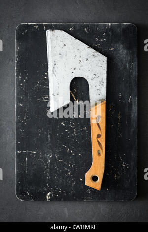 Old butcher axe or meat cleaver on black cutting board. Vertical, top view - Stock Photo