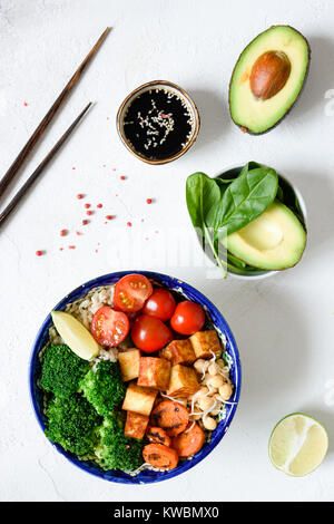 Buddha bowl with roasted carrots, avocado, tomato, broccoli, sprouts and tofu cheese. Vegetarian bowl. Top view - Stock Photo