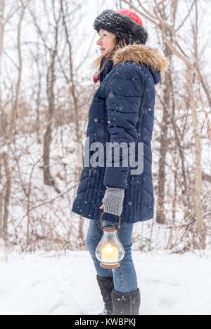 woman enjoying the beauty of fresh falling snow on wooded path holding lantern - Stock Photo