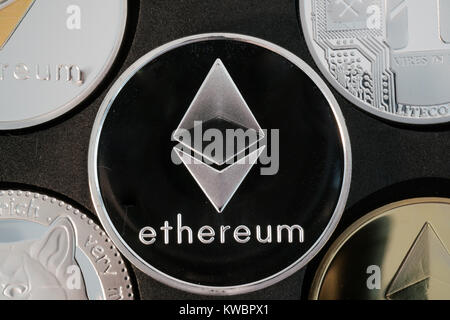 Ethereum cryptocurrency real silver coin in middle of other crypto closeup - Stock Photo