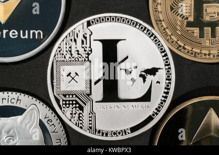 Litecoin cryptocurrency real silver coin in middle of other crypto closeup - Stock Photo