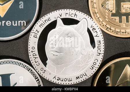 Dogecoin cryptocurrency real silver coin in middle of other crypto - Stock Photo