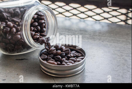 Close up of coffee beans in bottle cap and bottle on concrete floor at the coffee shop with copy space. - Stock Photo