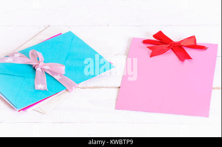 Bunch of multicolored letters tied together with pink ribbon and bow near a blank pink paper note with a red bow, - Stock Photo