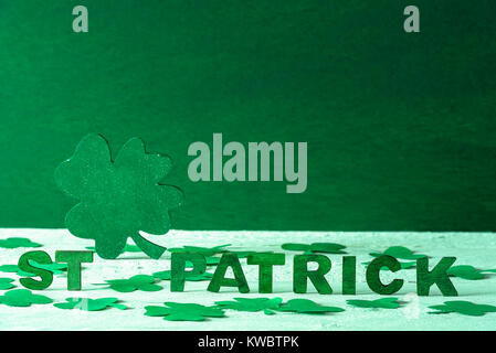 The words St Patrick written in green wooden letters and a big green clover in the back, surrounded by paper shamrocks, - Stock Photo