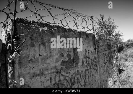 Barbed wire on cement fence. Monochrome silhouette photo - Stock Photo