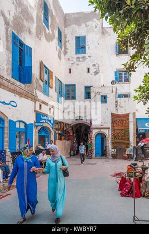 Two women walking through a square, Essaouira, Morocco, North Africa - Stock Photo