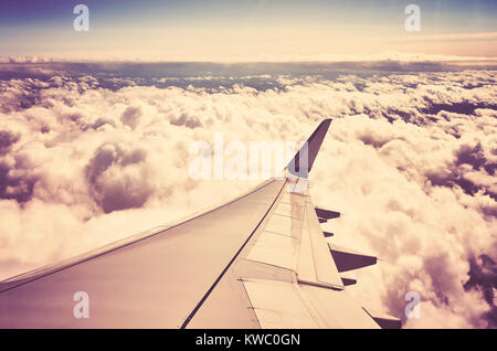 A plane wing above the clouds seen through a window of an aircraft, color toned travel concept picture. - Stock Photo