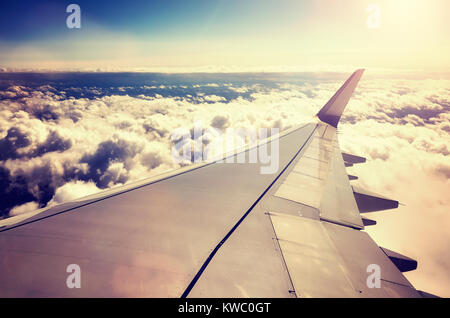 A plane wing above the clouds at sunset seen through a window of an aircraft, color toned travel concept picture. - Stock Photo