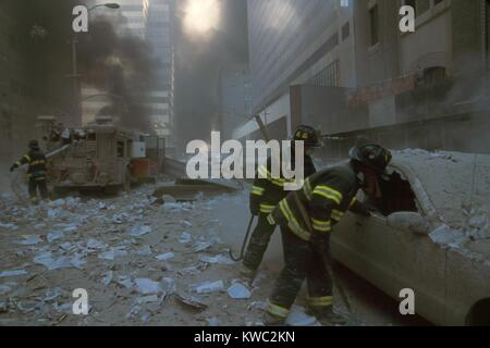 NYC firemen checking a car on Barclay Street after the 9-11 terrorist attack on World Trade Center. In the mid-ground fireman pulls a water hose from fire truck. View is toward West Broadway and includes WTC 7, on right, clad in red exterior masonry. WTC 7 collapsed at 5:20 PM on Sept. 11, 2001, due to fires ignited by debris from the North Tower (WTC 1) destruction earlier in the day. (BSLOC 2015 2 53)