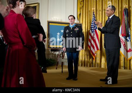 Former Staff Sergeant Clinton Romesha receives the Medal of Honor at the White House. President Obama applauds at - Stock Photo