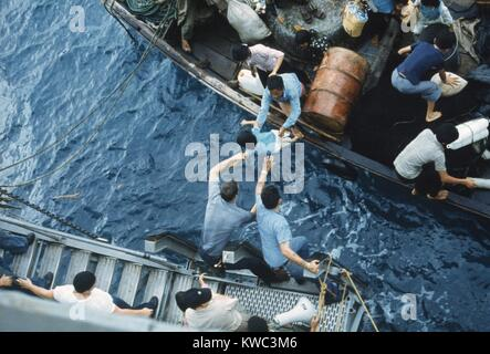 Assistance to 'Boat People', in a small craft on South China Sea, April 3, 1975. Crewmen of the amphibious cargo - Stock Photo