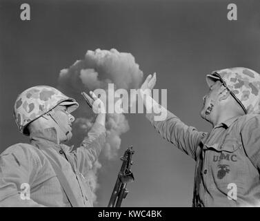 Soldiers pose below an atomic cloud at the Nevada Proving Ground. Soldiers conducted maneuvers in the vicinity of - Stock Photo