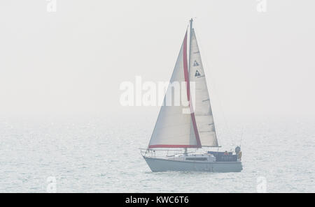 Small yacht with sails up on the sea in mist and fog. - Stock Photo