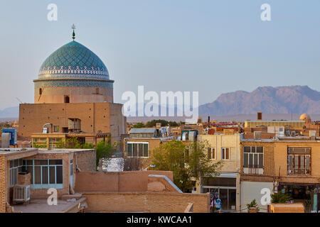 View of rooftops in Yazd old clay city of Iran, with  Jameh Mosque and mountains behind. - Stock Photo