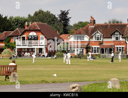 Bowler and fielders in action at an English Cricket match with pavilion and houses around the green - Stock Photo