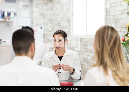 Young oculist woman selling glasses to couple at store - Stock Photo
