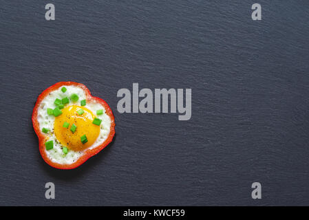 Fried eggs with red sweet pepper and chives on a black slate background. Top view. - Stock Photo