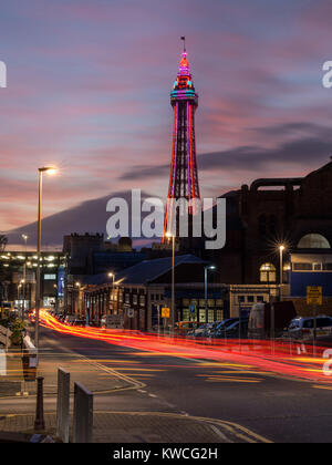 Blackpool Tower lit up at dusk with car light trails in foreground - Stock Photo