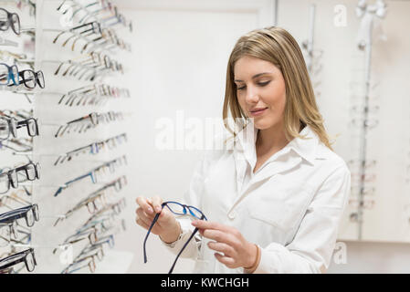Optometrist woman looking glasses at display in optical store with lab clothing - Stock Photo