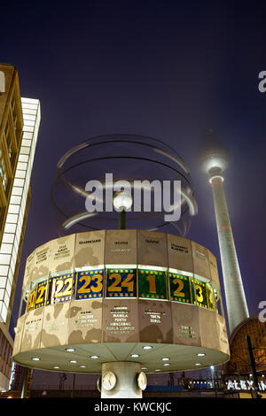 The famous world time clock and the TV tower at Berlin Alexanderplatz at night. - Stock Photo