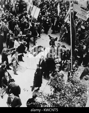 Crowd shouting and pointing towards a dead man and a woman lying in an Athens street. After liberation from the - Stock Photo