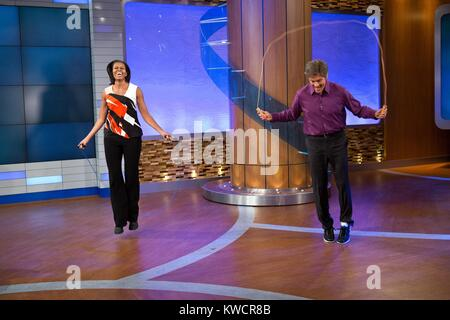 First Lady Michelle Obama and Dr. Mehmet Oz jump during a taping of the 'Dr. Oz Show'. First Lady's discussed improvements - Stock Photo