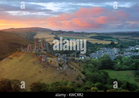 CORFE CASTLE, DORSET, ENGLAND: Ruins of Corfe castle and village at sunrise - Stock Photo