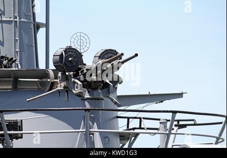 Machine gun on deck of a battleship in the harbor of San Francisco, California - Stock Photo