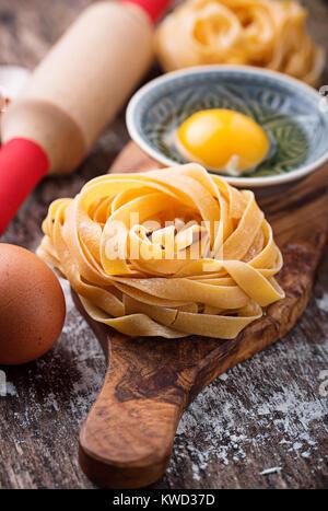 Raw pasta tagliatelle and eggs - Stock Photo