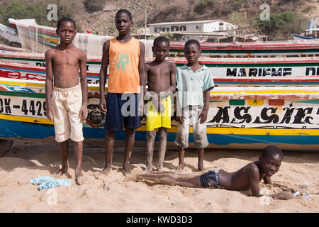 Group of young people next to fishing boats on a beach in Dakar, Senegal - Stock Photo