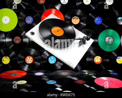 A floating record player in front of a wall of old vinyl records - Stock Photo