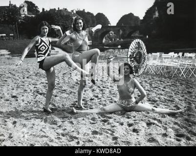 Acrobatic French women pose in the latest fashionable bathing suits on the sand beach at Dieppe. Ca. 1925. (BSLOC - Stock Photo