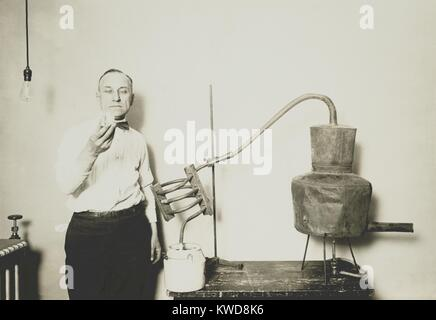 Moonshine still recently confiscated by the Internal Revenue Bureau. An employee holds a glass of alcohol distilled - Stock Photo