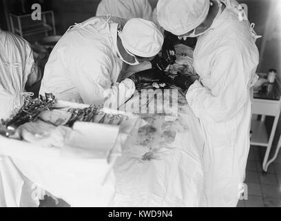 Attending surgeon leans over to work closely over a patient's abdomen. The surgical field is stained with blood. - Stock Photo