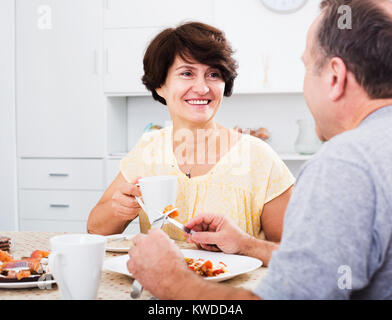 Glad senior woman eating lunch and listening to her husband at home - Stock Photo