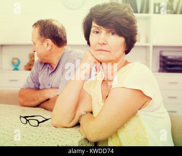 Sad mature woman experiencing family problems with her mature partner indoors - Stock Photo