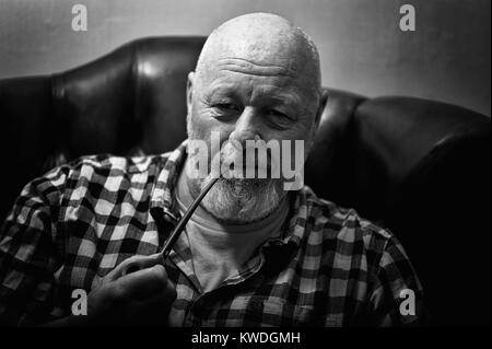 A mature male sitting in a wing back chair holding a pipe, in a reflective mood. - Stock Photo