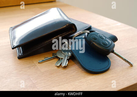 Wallet, car key, house keys and mobile phone on a table together in such a way that looks like someone is about - Stock Photo