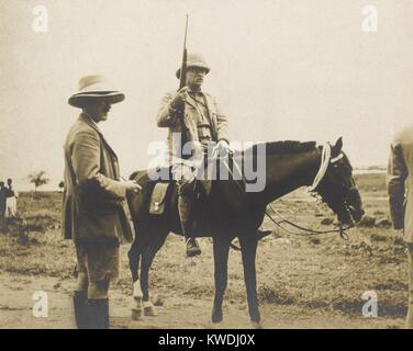 Theodore Roosevelt on horseback and holding a rifle during his safari. Standing by him is his son Kermit, who was - Stock Photo